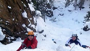 Two ice climbers summiting their cliff.